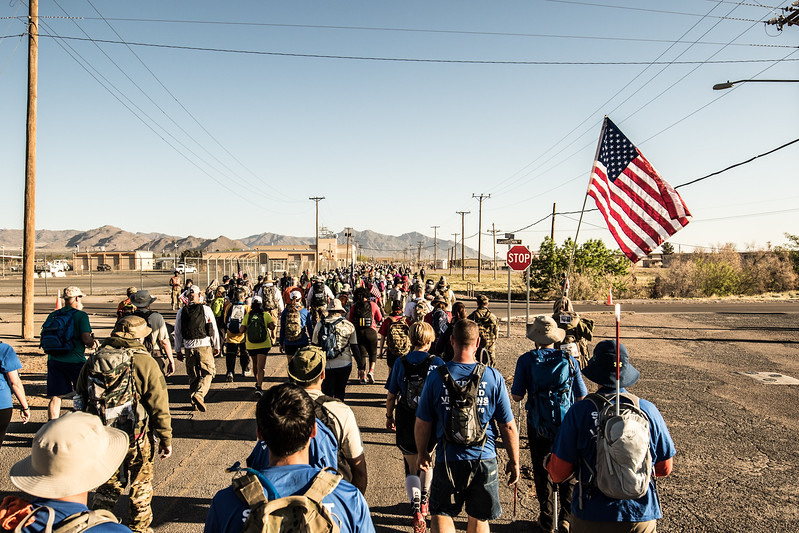 Thousands of participants of the Bataan Death March crowd the street.  An American Flag is carried by a participant and it waves over the BVA members.
