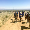 The BVA crew hikes uphill on the sandy road.  A desert mountain range spans the horizon.