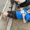 Lonnie Bedwell lies on the curb looking up at the camera, smiling with two thumbs up!
