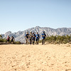 The BVA crew heads towards the camera down a dirt trail.  Mountains tower in the background.