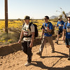 Kevin, Steve Baskis, Lonnie Bedwell and Nate Gorham trekking down the road.  Yellow poppies bloom across the desert landscape.