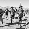 A black and white photo of the BVA crew trekking towards the camera.  The desert mountains spread across the horizon.