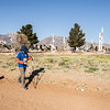 Tim Hornik treks down a dirt trail with the White Sands Missile Park in the background.