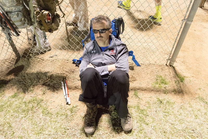 Lonnie Bedwell sits up against a fence resting before the Bataan Death March.