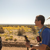 Steve Baskis trekking down the road.  Yellow poppies bloom across the desert landscape.