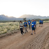 The BVA crew hikes adown the sandy road during the last mile of the Bataan Death March.  A bright sun sets behind the desert mountain range.