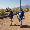 Dan Standage and his wife Nancy trekking down the road.  Yellow poppies bloom across the desert landscape.
