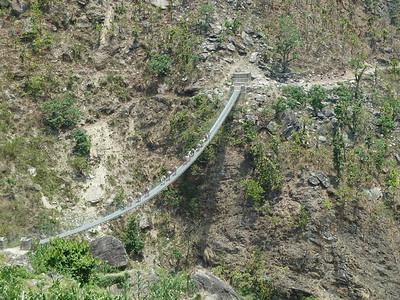 A mule train crosses a long bridge.