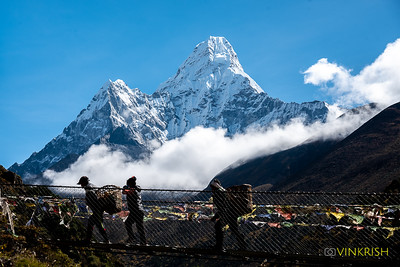 Porters cross the bridge to Pangboche as Ama Dablam shines