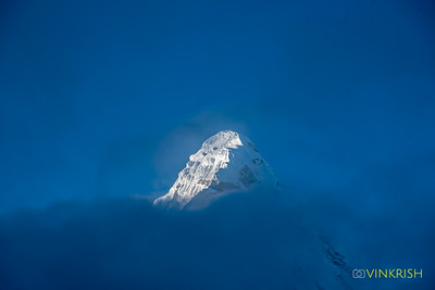 The morning sun hits Ama Dablam even as the fog tries to mask it