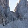 Three hikers heading up the path toward the spectacular notch in the Cima del Focobon, the Passo della Farangole