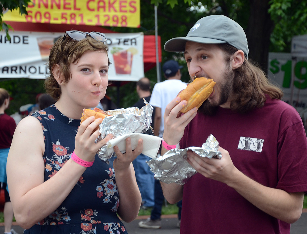 . Rhi Strother(l)and Jesse Krzywicki enjoy their pork roll sandwiches at the Official 4th Annual Pork Roll Festival in MIll Hiil Park in Trenton on Saturday. gregg slaboda photo