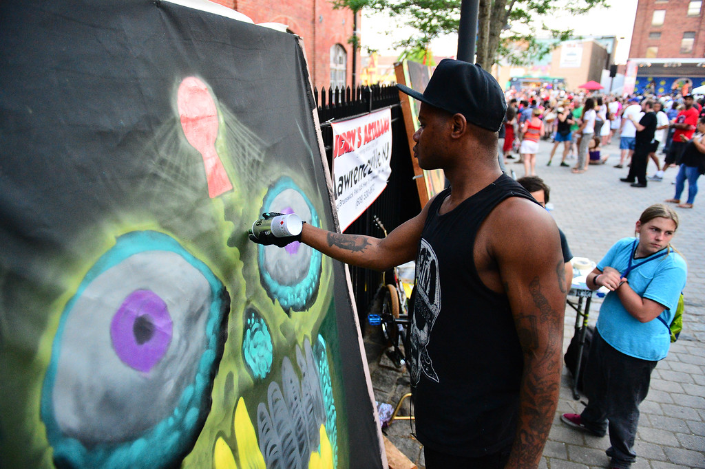 . Billy Brown is seen working on a mural at Art All Night in Trenton on June 18, 2016. (Scott Ketterer - For The Trentonian)