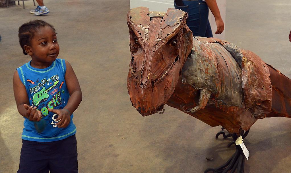 . Ka-Leal Brown checks out the Steel Tyranosaur sculpture at Art  All Night . gregg slaboda photo