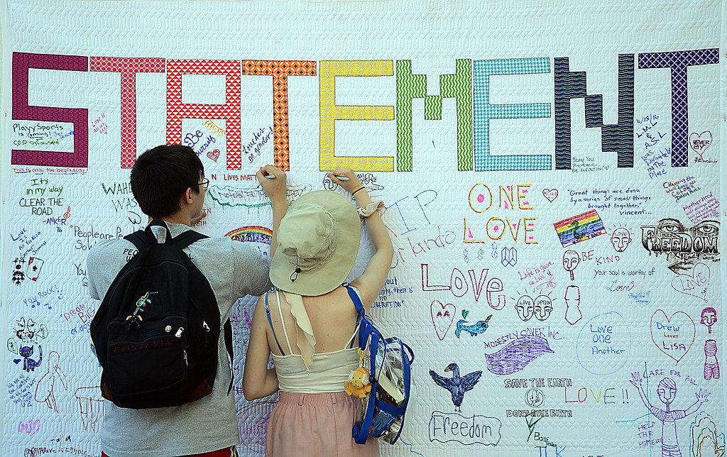 . People sign a mural at Art All Night. gregg slaboda photo