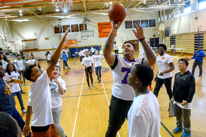 Dion Dawkins shoots the ball during a game of knockout basketball at Grice Middle School in Hamilton Friday. The Bills offensive lineman visited the school for a STEM program.<br /> John Berry — The Trentonian