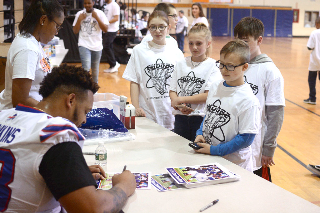 . Buffalo Bills offensive lineman Dion Dawkins signs photos during an appearance at Grice Middle School in Hamilton.