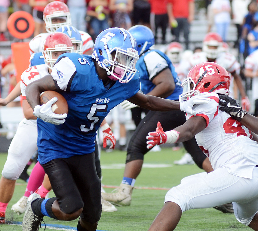 . Ewing`s Edamiyon Doggett(l) carries the ball against Lawrence. gregg slaboda photo