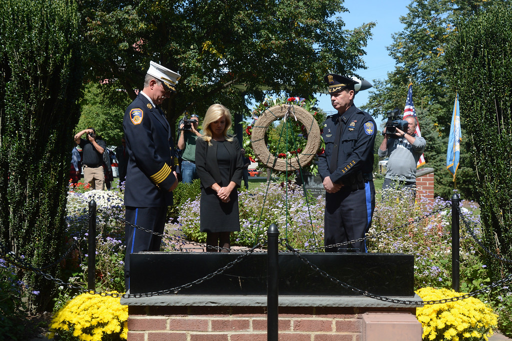. Hamilton District 9 Fire Chief Mark Antozzeski, Mayor Kelly Yeade, and Police Chief James Collins observe a moment of silence after placing a wreath at the September 11th memorial in Veterans Park Monday on the 16th anniversary of the September 11th terrorist attacks.