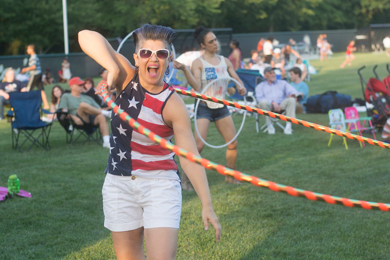 A hula hoop performer dances while The Heartbeats play before the fireworks at Hamilton's Independence Day celebration Monday at Veterans Park. <br /> John Berry - The Trentonian