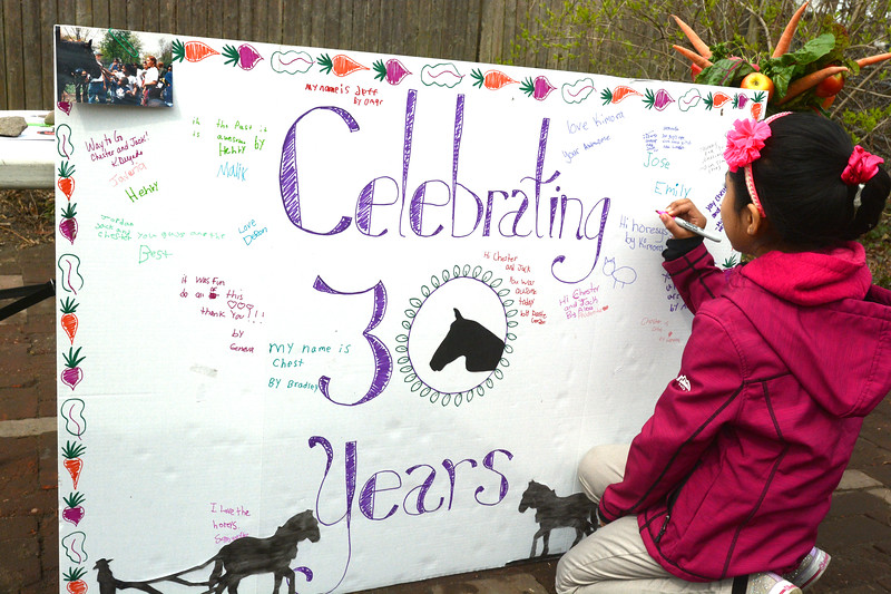 A student signs the board commemorating a 30-year collaboratiion between Howell Farm and Isles.<br /> John Berry — The Trentonian
