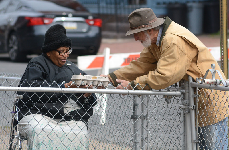 Pete Watson from Howell Living History Farm gives eggs to Ethel Williams as she watched Howell teach farming techniques at the Chestnut Avenue Community Garden, which Williams lives next to.<br /> Isles and Howell Living Farm worked together to plow and teach local students about farming Thursday. <br /> John Berry — The Trentonian