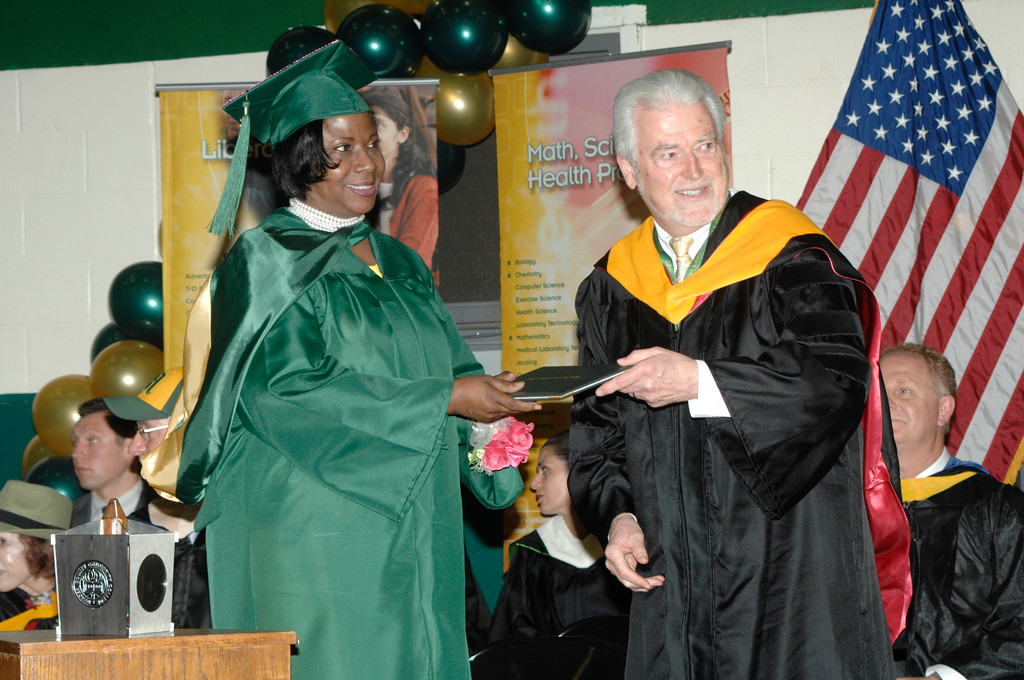 . MCCC graduate Hope Jarvis receives her diploma from Dr. Walt MacDonald, treasurer of the MCCC Board of Trustees.Courtesy of Mercer County Community College