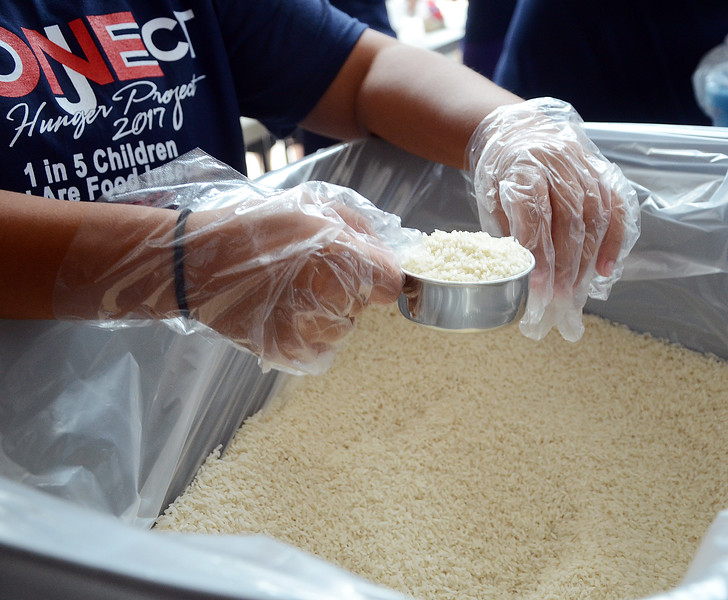 One Project volunteer scoops rice as they package meals for 100,000 families. gregg slaboda photo