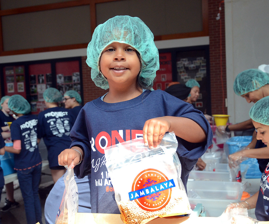 . Kiran Bajnath,21/2 years old, helps package meals for 100,000 families at the One Project event at Robbinsville High School on Saturday morning . gregg slabopda photo