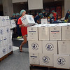 A volunteer carries a box of food at the One Project Nj at Robbinsville High School on Saturday. gregg slaboda photo