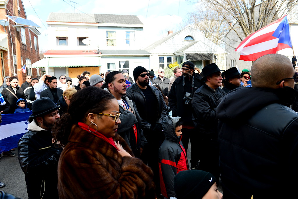 . Attendees place their hands over their hearts during the singing of the national anthem at a Saturday event honoring the efforts of the city\'s Puerto Rican community following the spraying of a swastika on a Puerto Rican flag that was painted on a building in the 100 block of Genesee Street . (Scott Ketterer - The Trentonian)