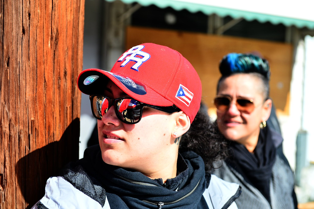 . Lizmary Rivera displays her Puerto Rican pride and flags are seen waving in the reflections on her sunglasses  at a Saturday event honoring the efforts of the city\'s Puerto Rican community following the spraying of a swastika on a Puerto Rican flag that was painted on a building in the 100 block of Genesee Street . (Scott Ketterer - The Trentonian)