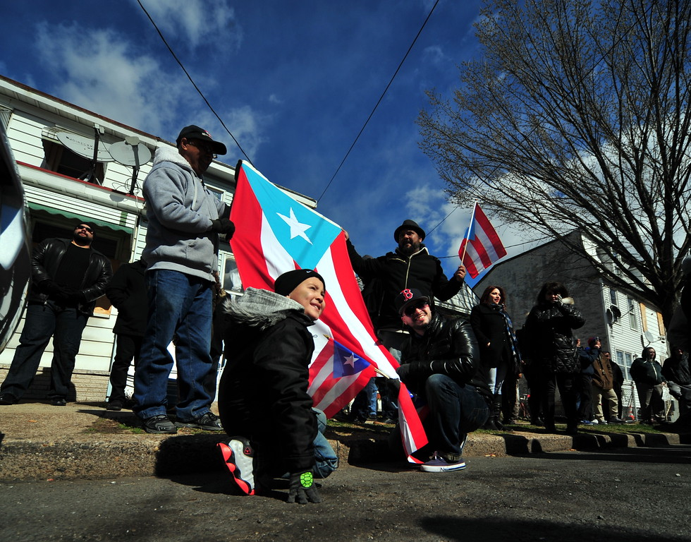 . Attendees display Puerto Rican flags at a Saturday event honoring the efforts of the city\'s Puerto Rican community following the spraying of a swastika on a Puerto Rican flag that was painted on a building in the 100 block of Genesee Street . (Scott Ketterer - The Trentonian)
