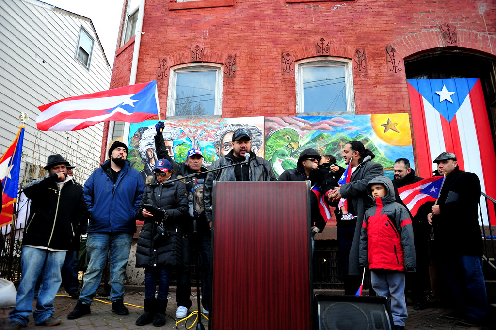 . Sam Kanig (center) speaks  at a Saturday event honoring the efforts of the city\'s Puerto Rican community following the spraying of a swastika on a Puerto Rican flag that was painted on a building in the 100 block of Genesee Street . (Scott Ketterer - The Trentonian)