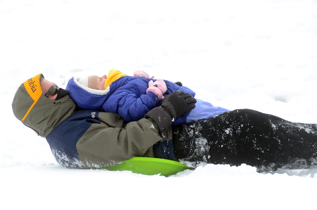 . A father and daughter have fun in the snow at Veterans Park. gregg slaboda photo