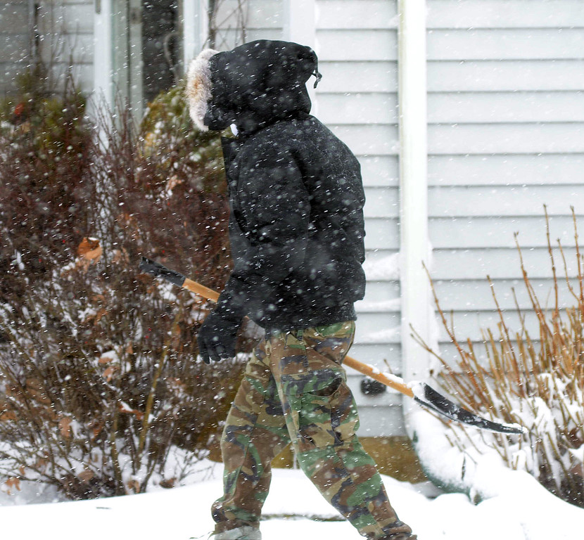 . A man carries his shovel in the Briarwood section of Hamilton. gregg slaboda photo