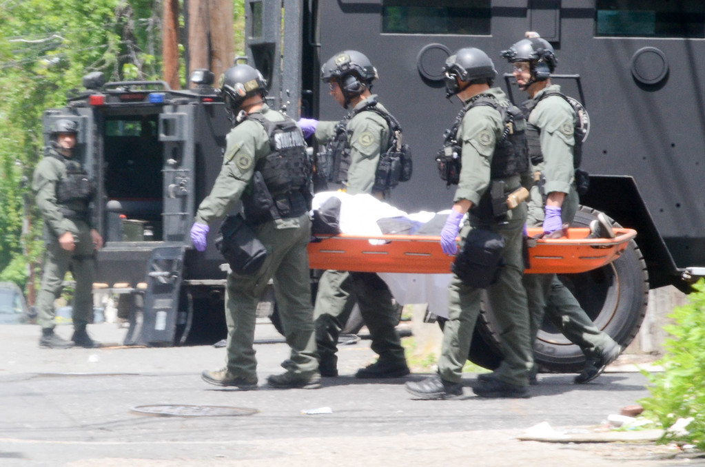 . New Jersey State Police  TEAMS unit officers are seen moving the body of a man killed during a shootout with police. The alleged shooter barricaded himself inside after a shootout with police on May 10, 2017. (Penny Ray - The Trentonian)