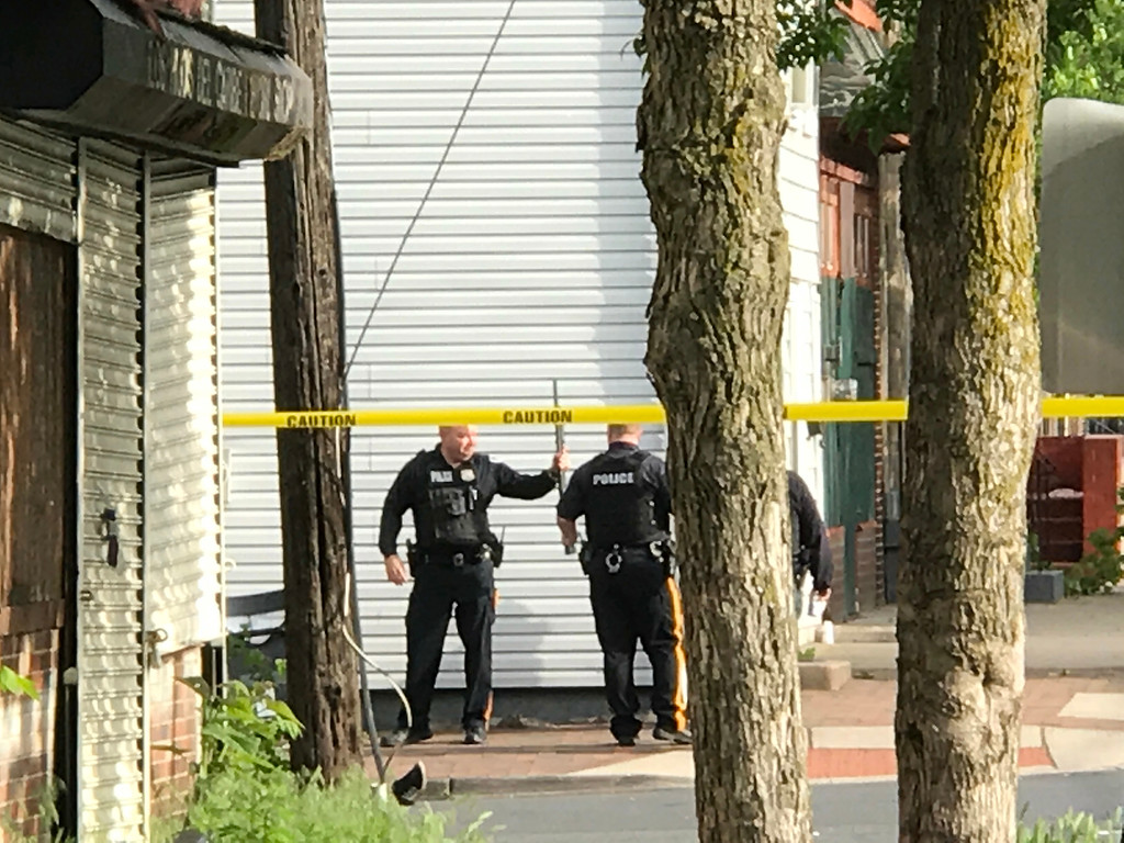 . Police guard the body of a homicide victim as the suspect is barricaded inside of a home on the 300 block of Centre St. in Trenton. 