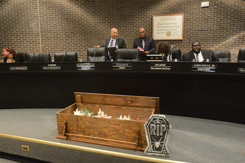 Trenton Schools Superintendent Frederick McDowell (center left) approaches his seat after the TEA placed a fake coffin in front of his seat to symbolize their desire to get rid of McDowell. <br /> John Berry — The Trentonian