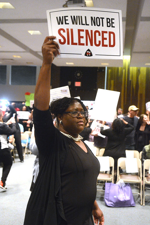 . TEA President Naomi Johnson-LaFleur holds up a sign before the Trenton Board of Education meeting Monday. 