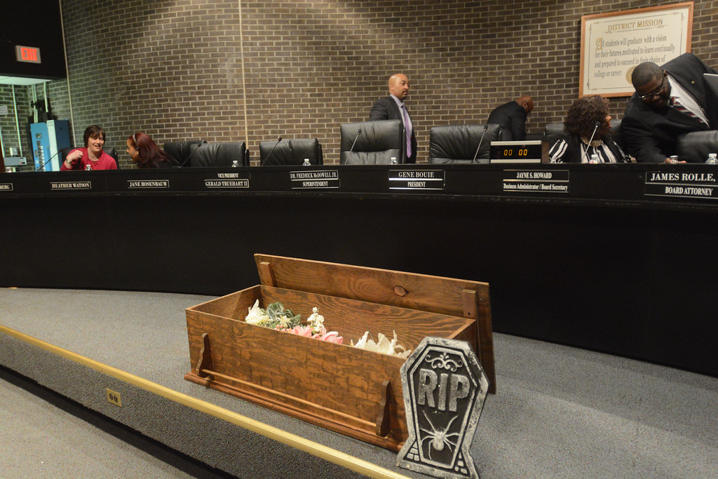 . Trenton Schools Superintendent Frederick McDowell (center) approaches his seat after the TEA placed a fake coffin in front of his seat to symbolize their desire to get rid of him. 