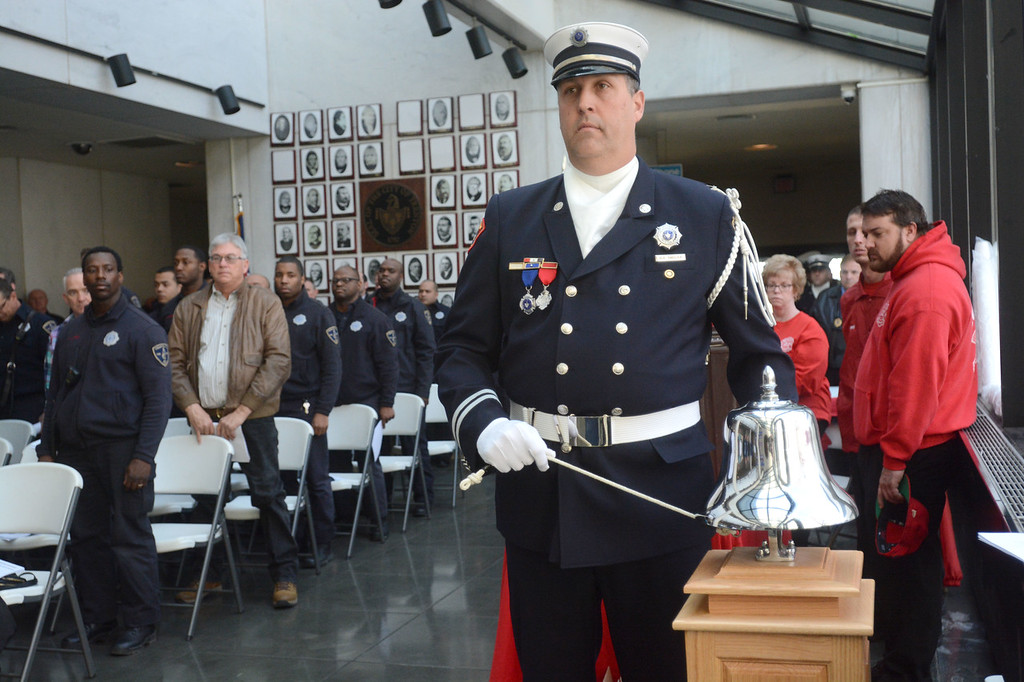 . Trenton Fire Deparment Captain David Smolka rings the five bells to honor fallen firefighters during the department�s annual memorial service Monday at City Hall.