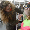 SFX makeup artist Meagan Impellizzeri puts a zombie bite on Raegan Jones at the Trenton Punk Rock Flea Market Saturday. <br /> John Berry — The Trentonian
