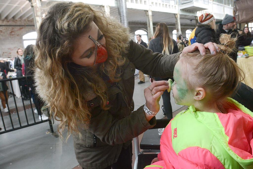 . SFX makeup artist Meagan Impellizzeri puts a zombie bite on Raegan Jones at the Trenton Punk Rock Flea Market Saturday. John Berry � The Trentonian