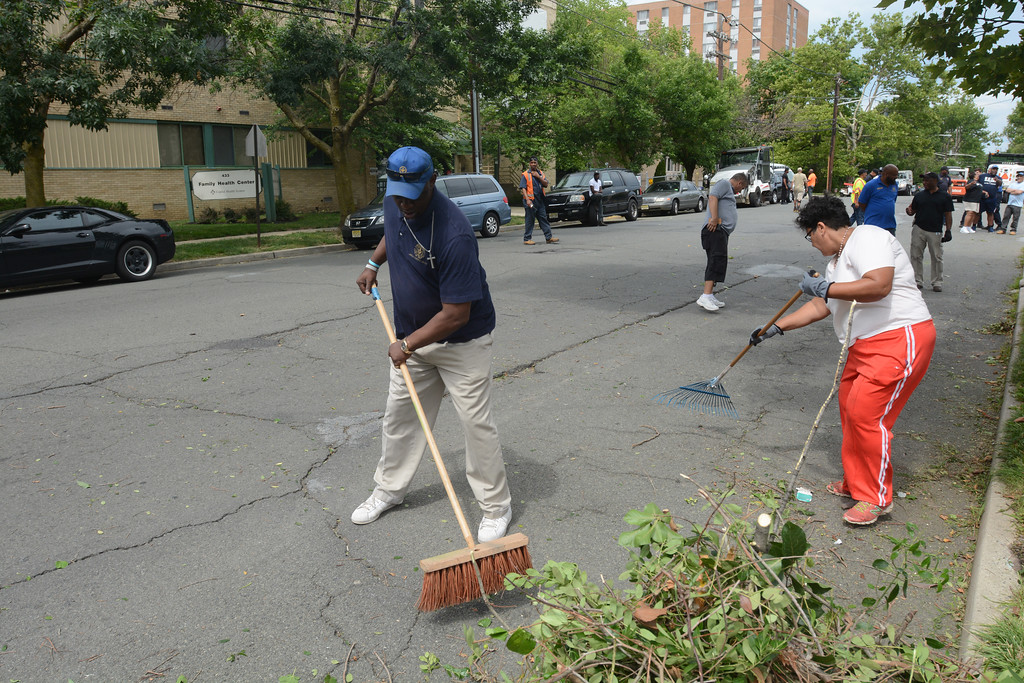 . Mayoral aide Andrew Bobbitt and other volunteers clean up some debris from the 400 block of Bellevue Ave. in Trenton during part of the city�s cleanup efforts Saturday. John Berry � The Trentonian