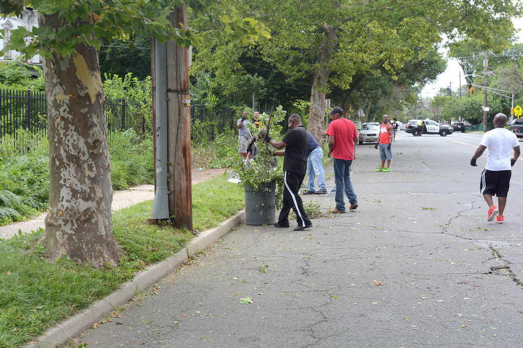 . Volunteers clean up some debris from the 400 block of Bellevue Ave. in Trenton during part of the city�s cleanup efforts Saturday. 