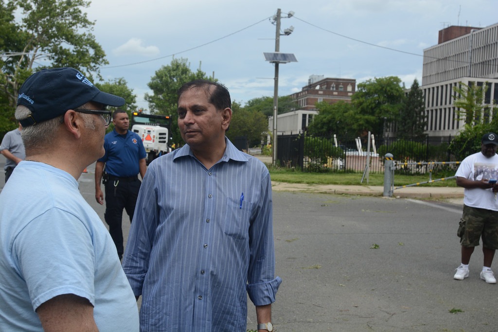 . Hemant Mehta, center, speaks with Trenton Mayor Reed Gusciora as volunteers clean up the 400 block of Bellevue Ave Saturday. Mehta is the owner of the abandoned Mercer Medical Center on that block. John Berry � The Trentonian