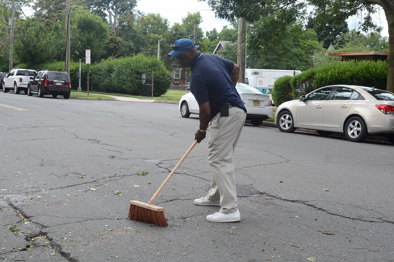 Mayoral aide Andrew Bobbitt sweeps along the 400 block of Bellevue Ave. in Trenton during part of the city's cleanup efforts Saturday. <br /> John Berry — The Trentonian
