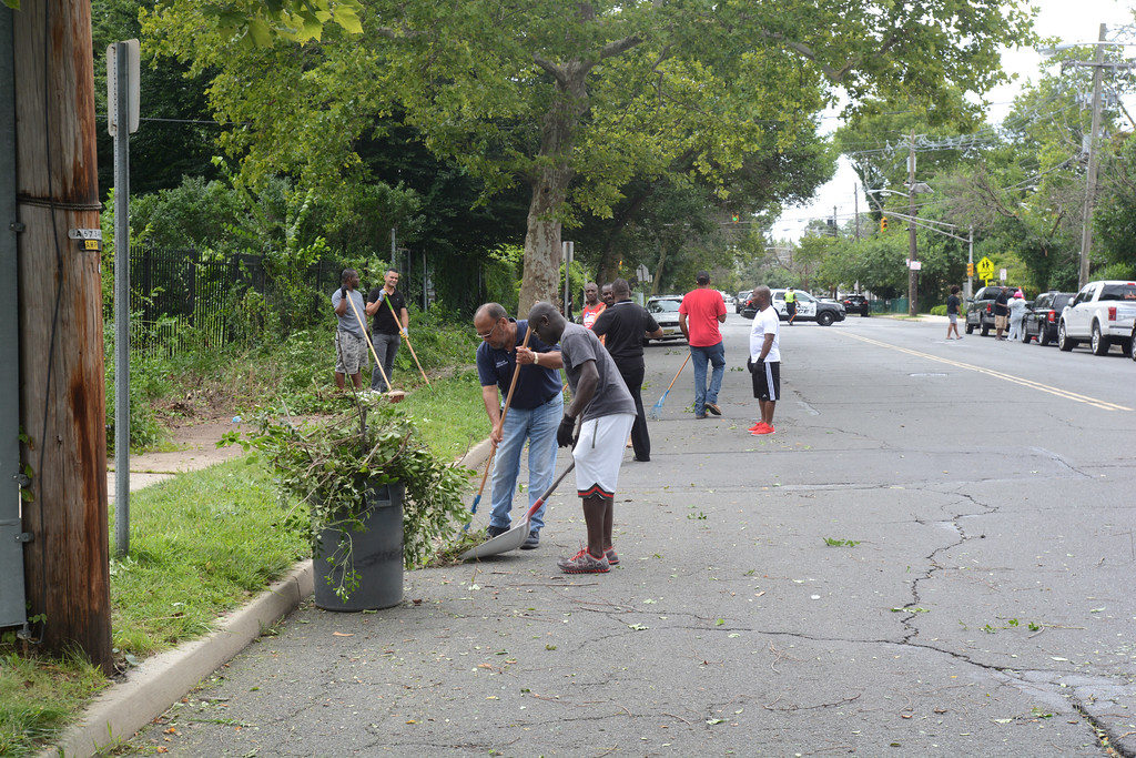 . Volunteers clean up some debris from the 400 block of Bellevue Ave. in Trenton during part of the city�s cleanup efforts Saturday. John Berry � The Trentonian