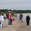 Spectators following their triathlete down the shoreline.